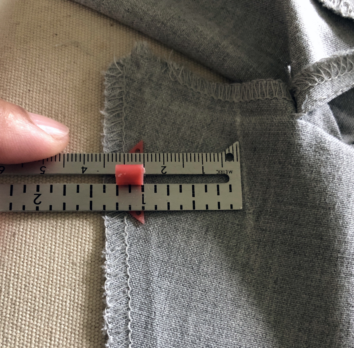 seam gauge measuring 1 inch from chalk mark to original inseam seamline on gray pants
