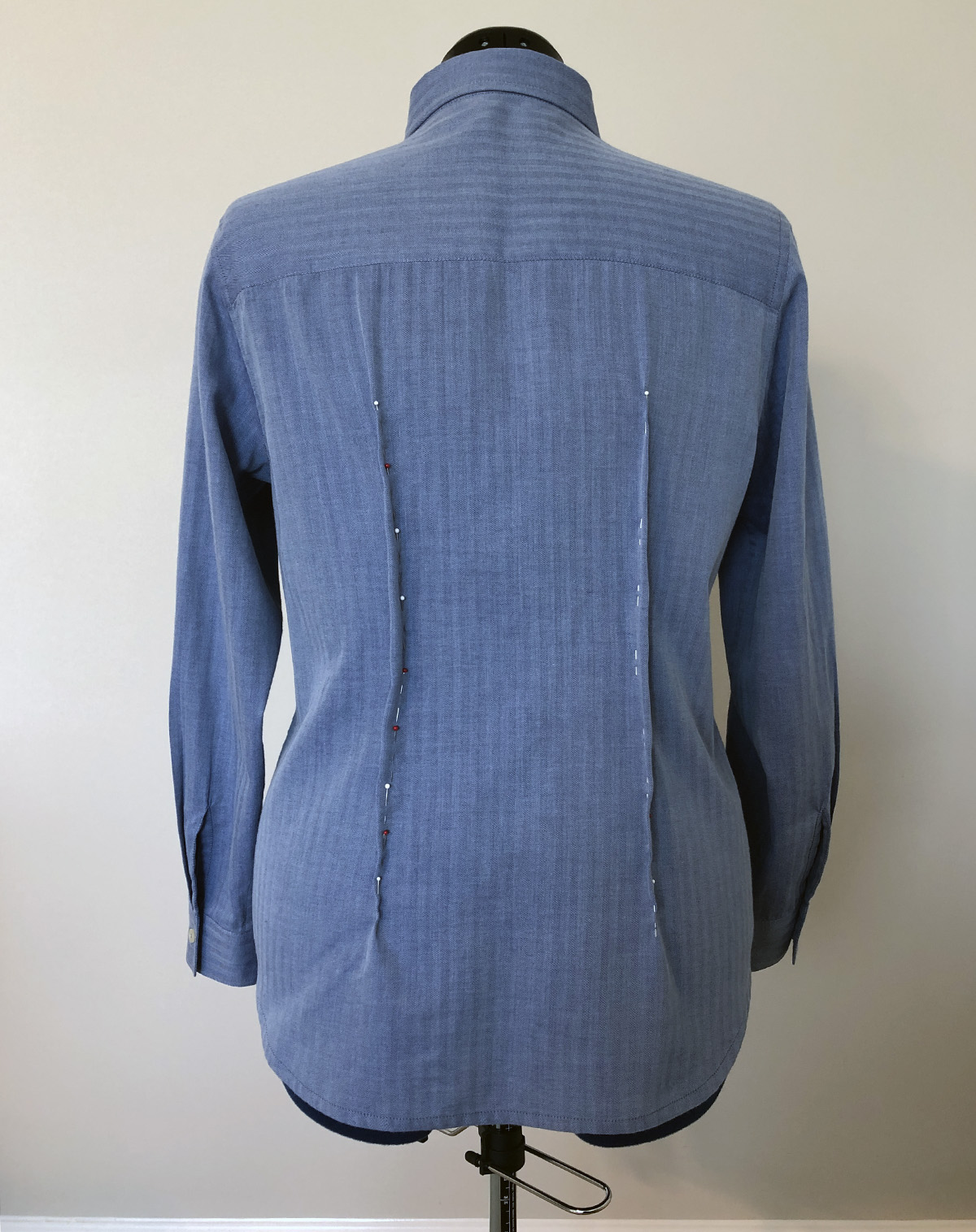 Back of blue dress shirt on dress form, with two vertical darts pinned in place
