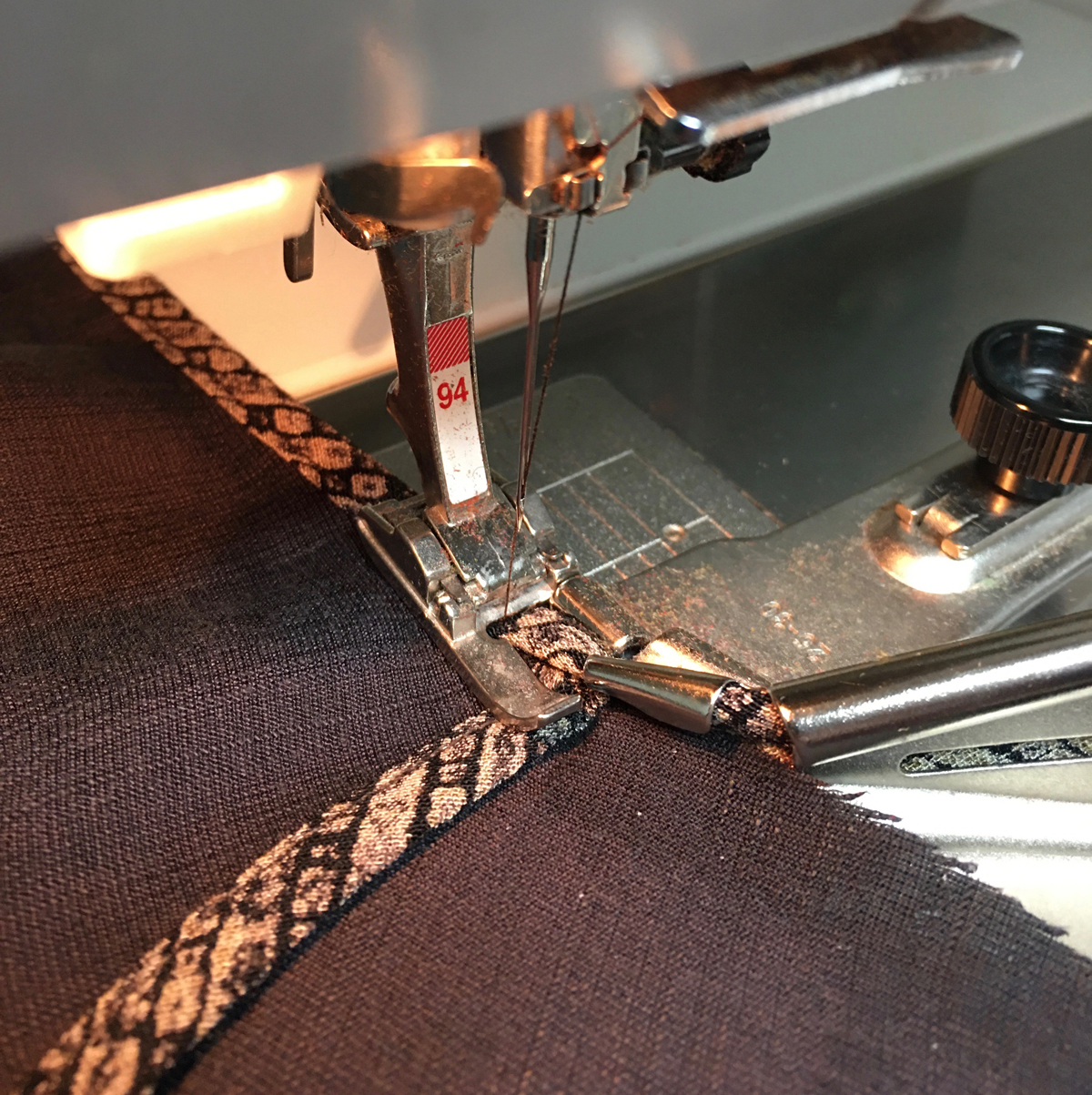 Binding being sewn onto fabric using a binding foot on the sewing machine