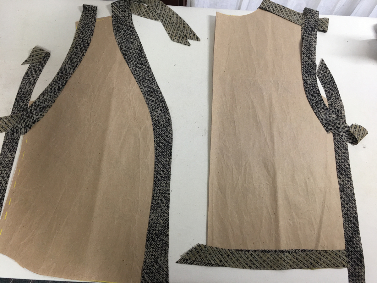 Separate bias strips lie on top of brown paper front and back top pattern pieces