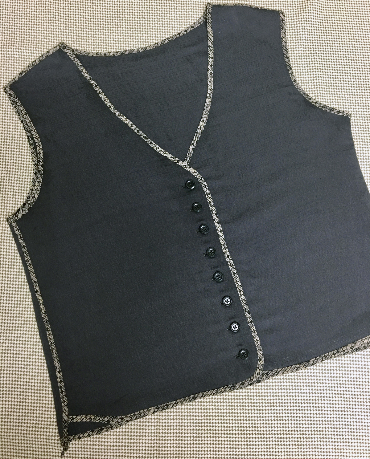 Finished dark gray vest lying flat on worksurface, all edges finished with light-colored print binding