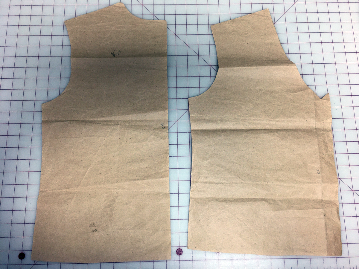 Two brown paper pattern pieces on a gridded surface