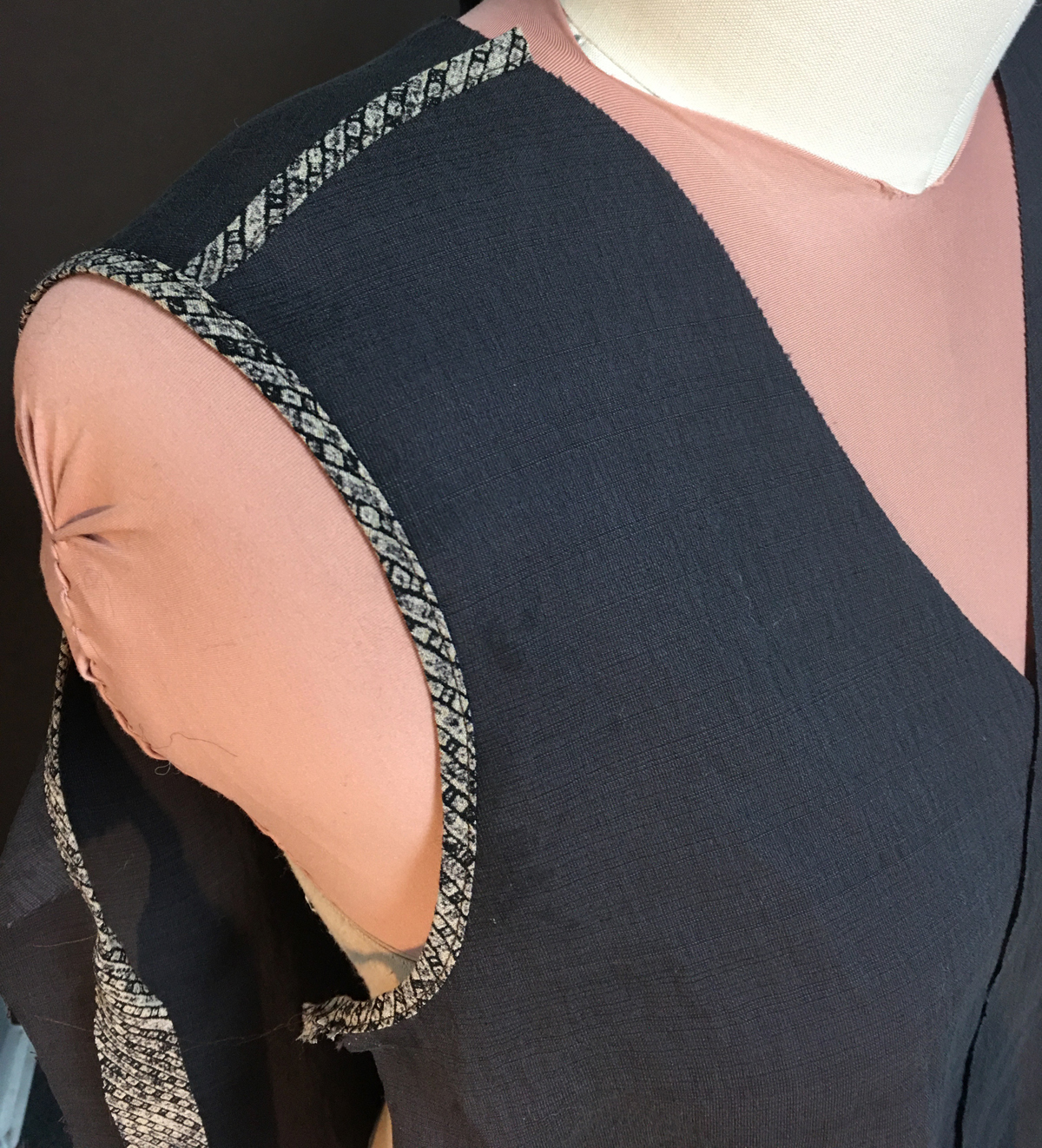 Closeup of bound shoulder and armhole edges of unfinished vest on dress form