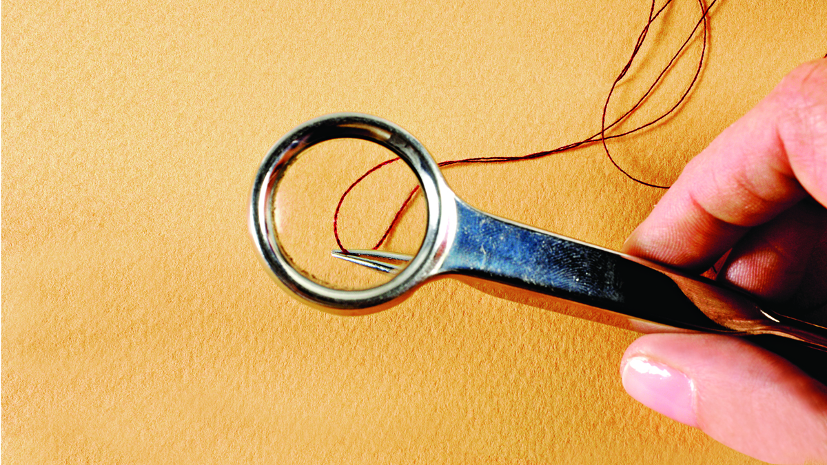 Thread on a needle under a handheld magnifying glass