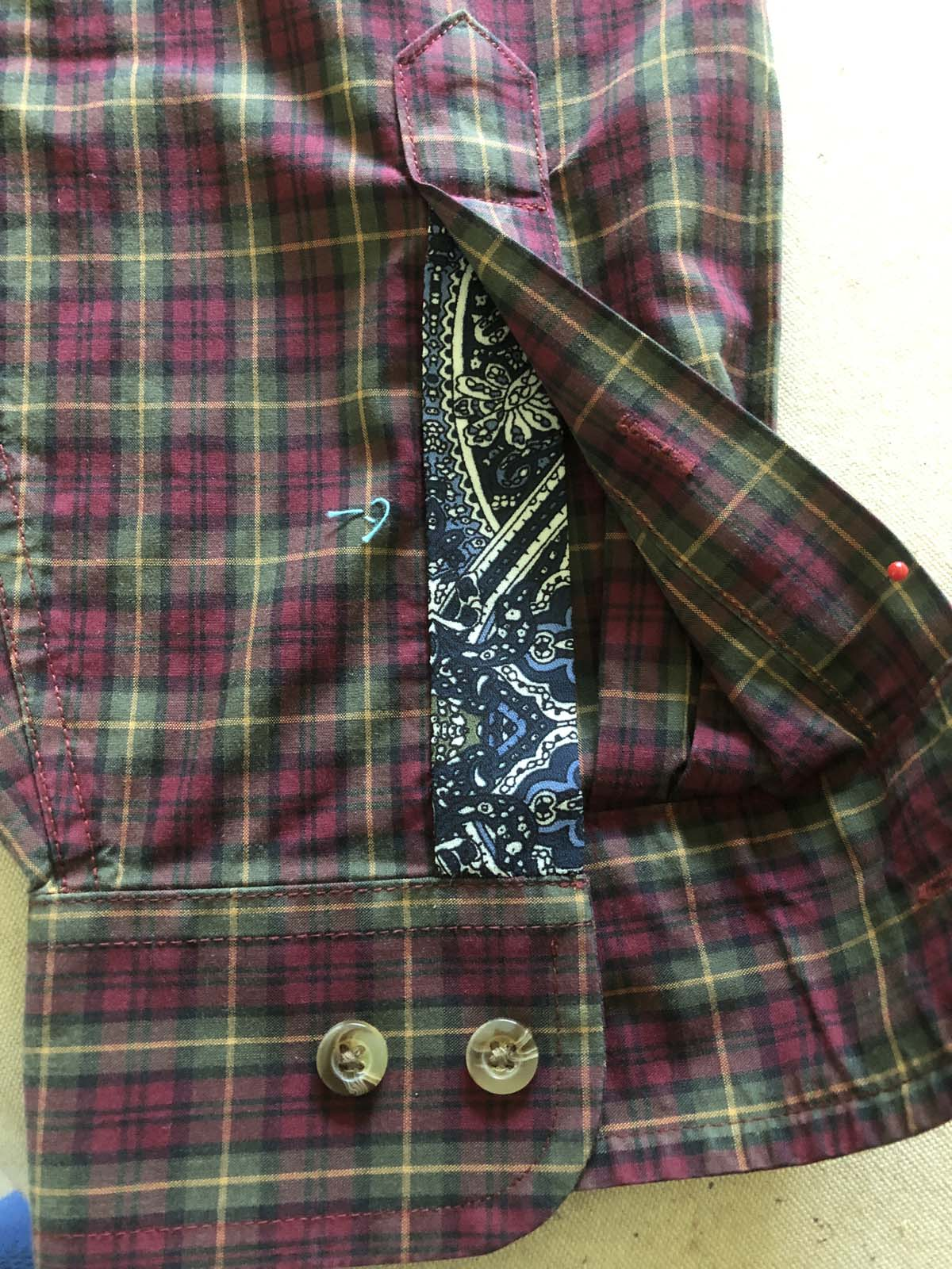 Appliqued right sleeve placket on red plaid shirt