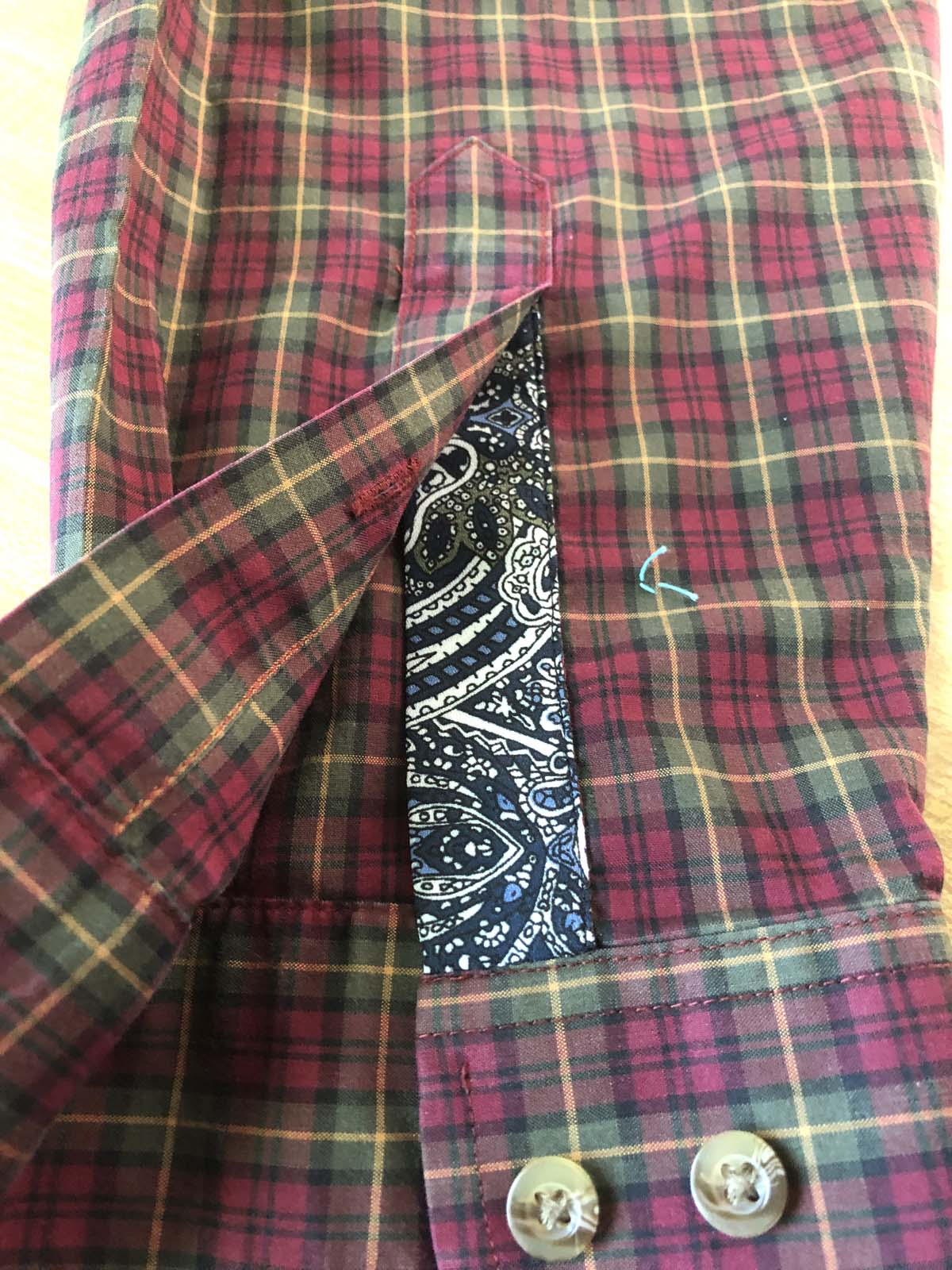 Appliqued left sleeve placket on red plaid shirt