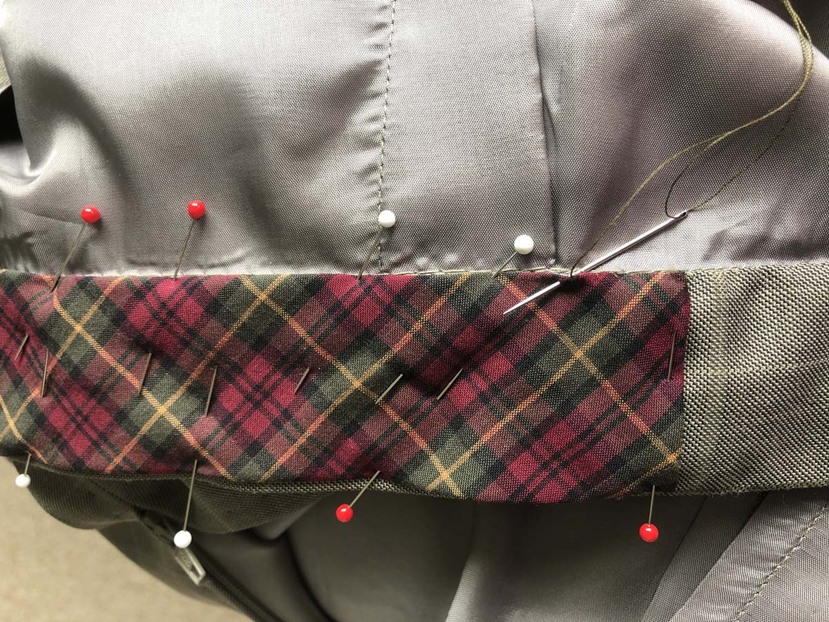 Bias strip cut from the plaid shirt pinned and sewn to the waistband, which originated from men's suit pants