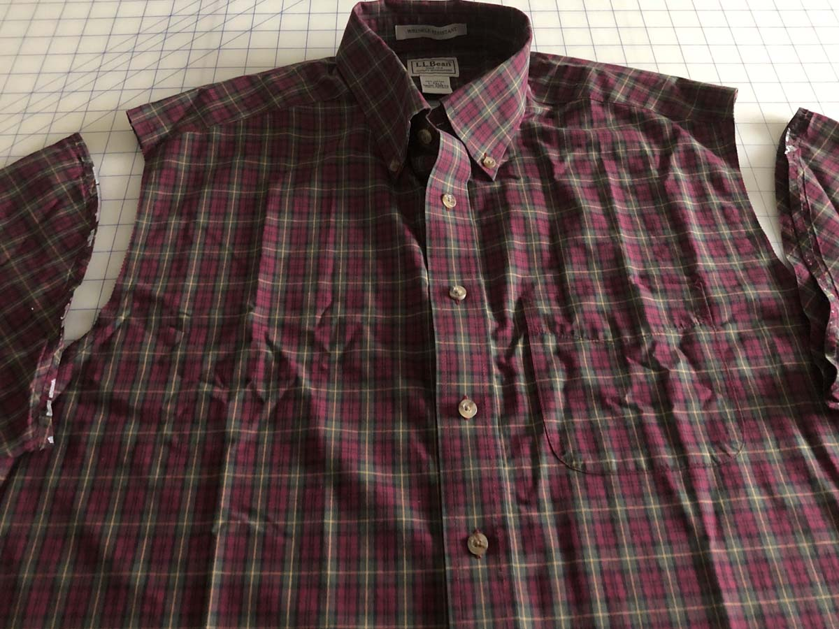 Shirt sleeves removed from red plaid shirt that is lying on gridded worksurface