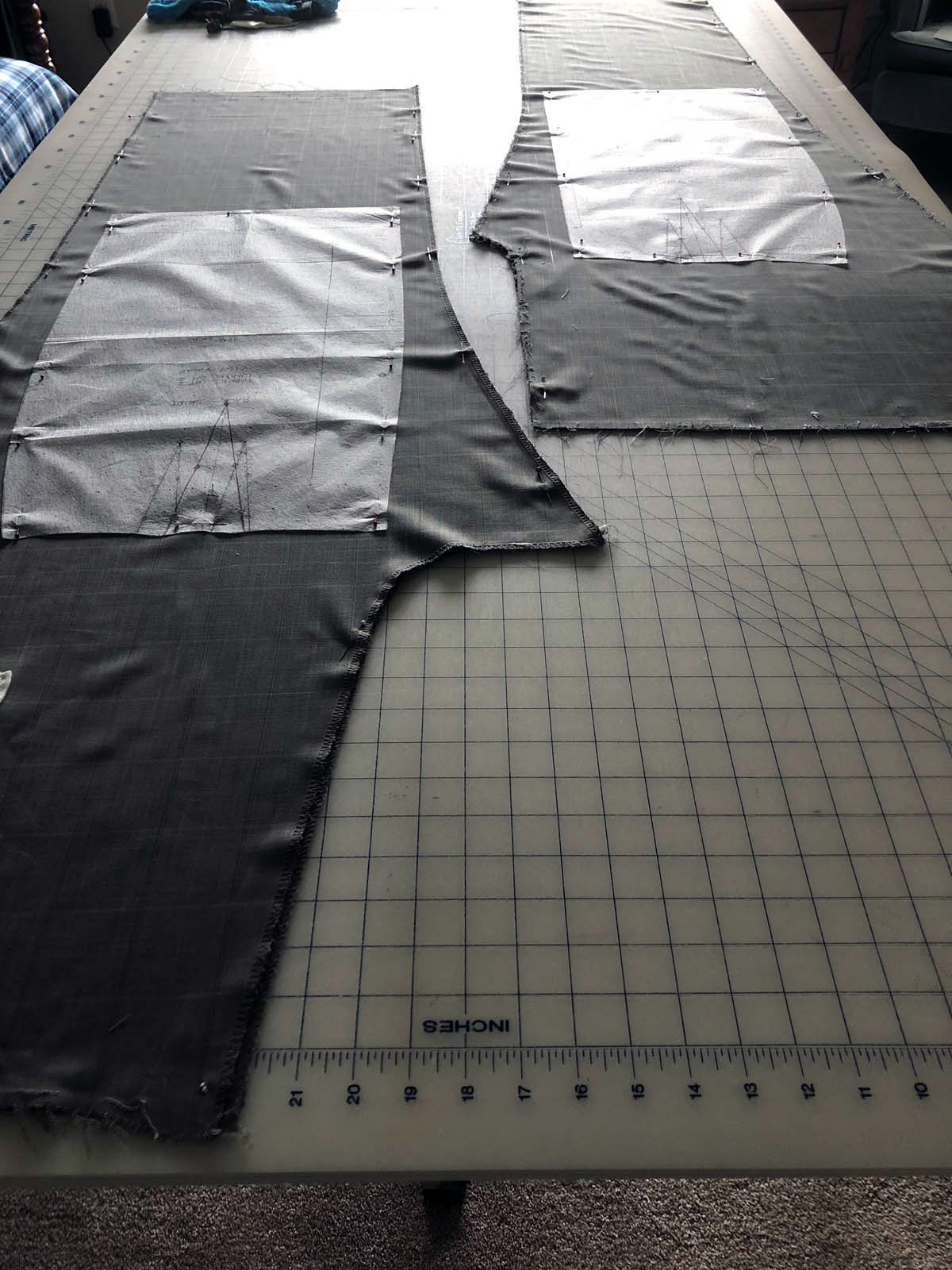 Deconstructed men's suit pant legs laid out with skirt patterns pinned on top