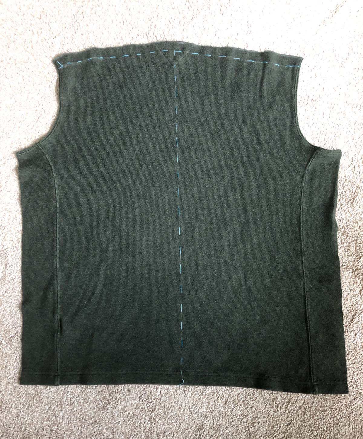 Center back and seam allowance along top edge marked on olive green sweater back