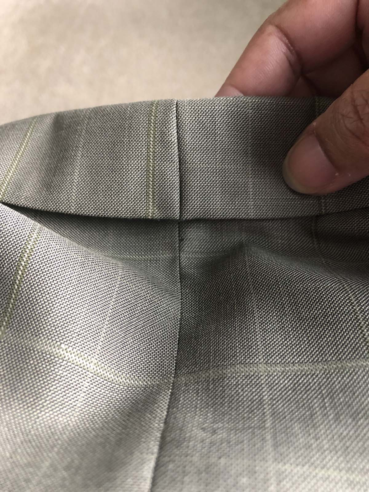 Upper collar of the men's suit jacket is taken in, shown from the right side