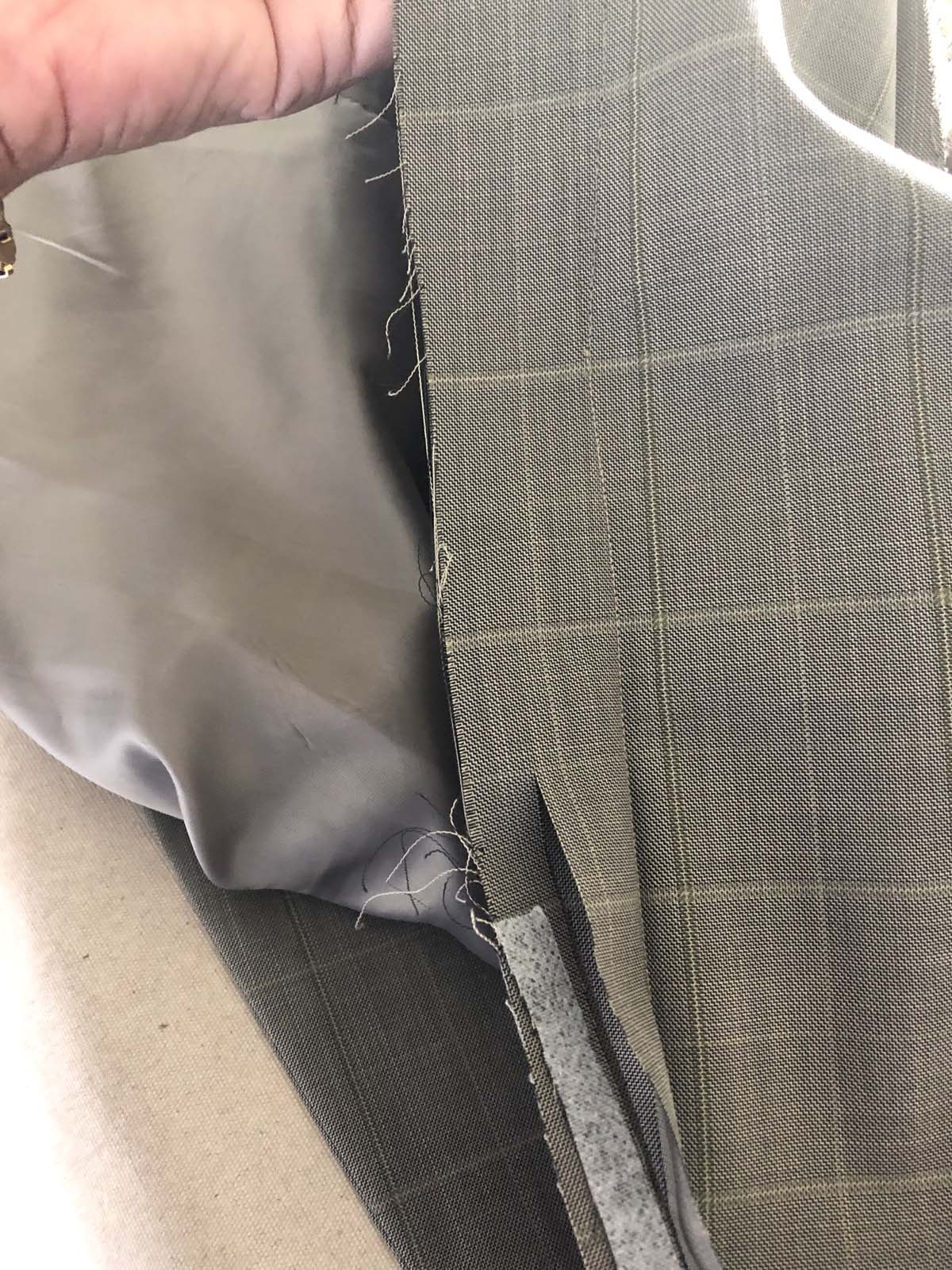 Removing excess seam allowances from the men's suit jacket