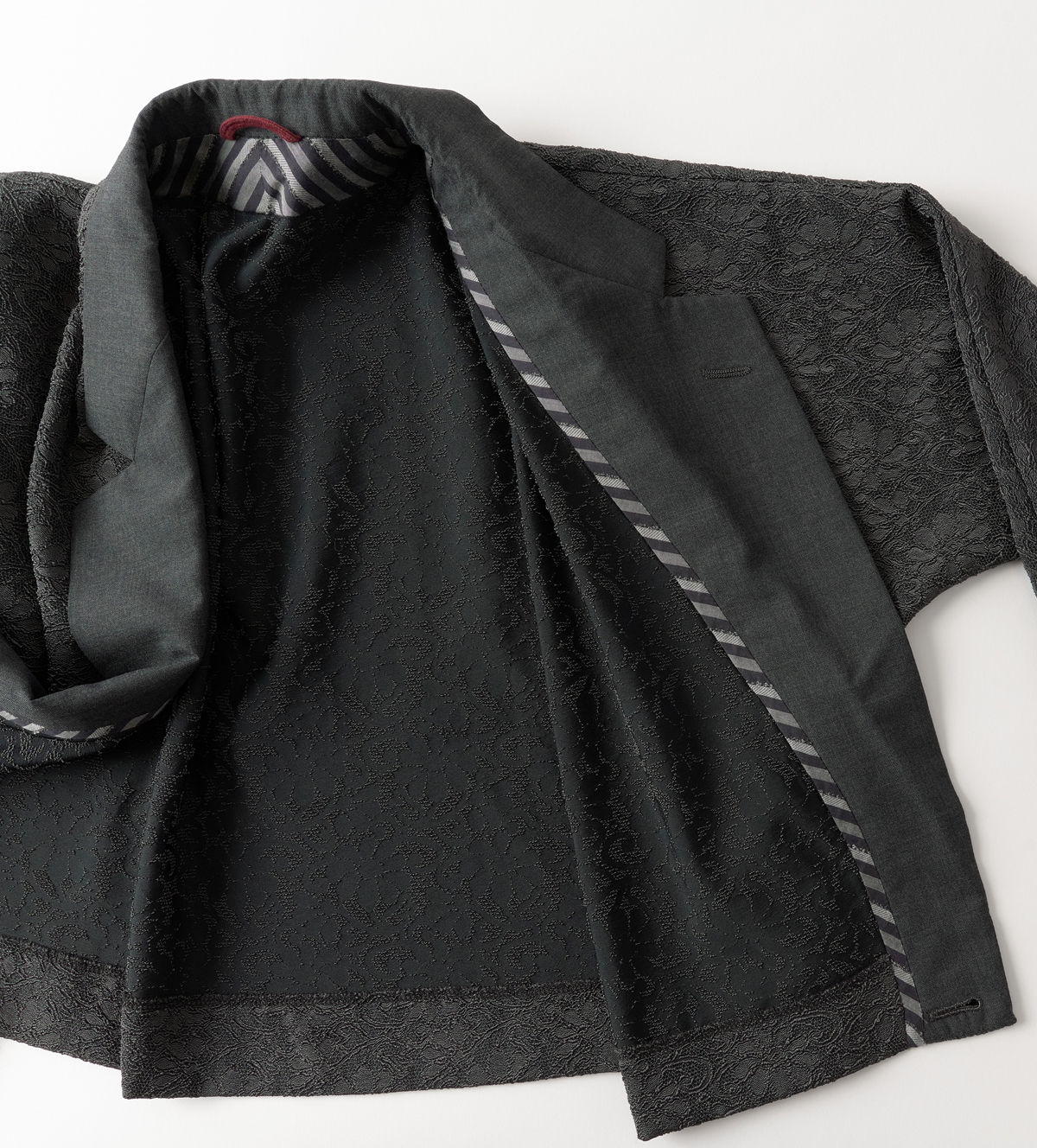 Women's Jacket lying opened on a table to reveal striped bias binding