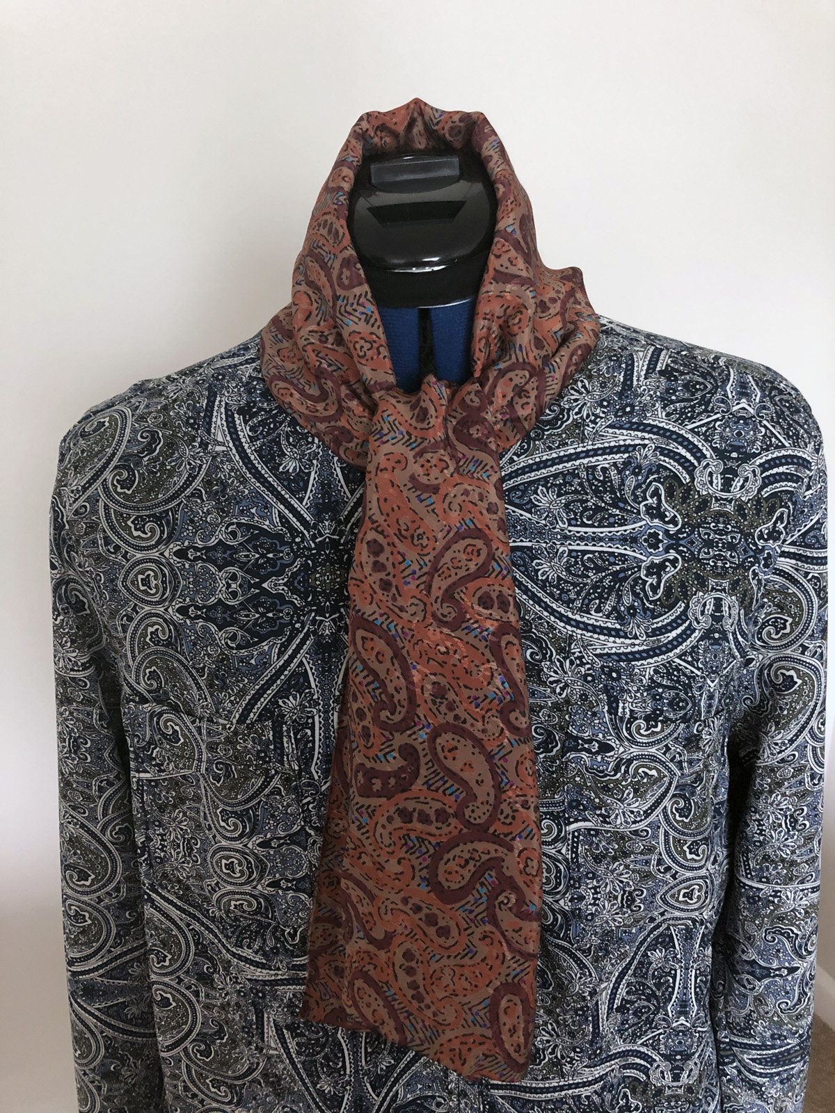Reddish-brown print fabric wrapped at neckline of blue paisley blouse on dress form