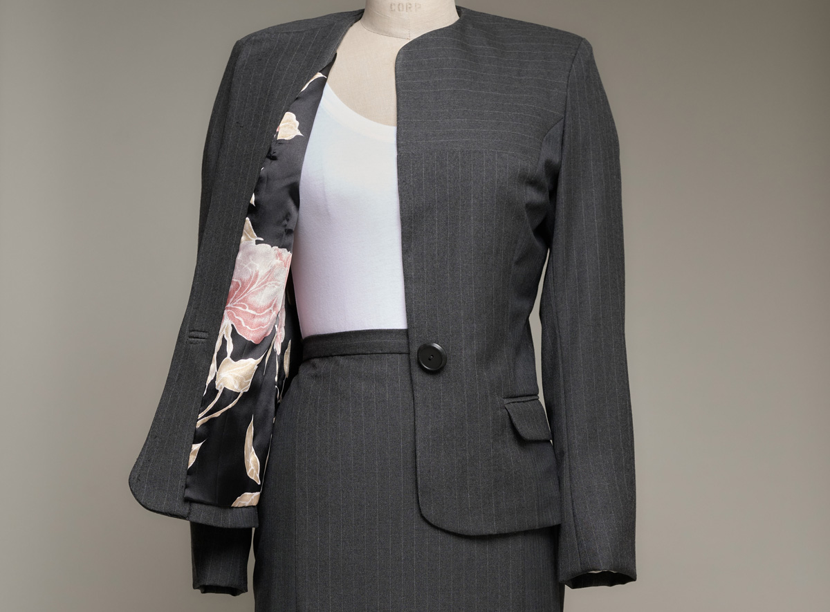 Women's suit jacket on dress form opened to reveal floral lining
