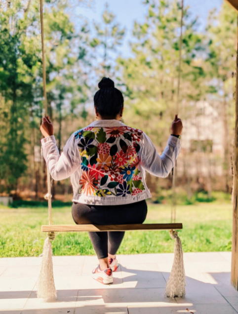 Woman wearing a Tabitha Sewer floral denim jacket sitting on a swing, with her back to the camera.