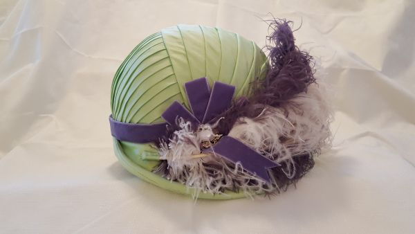 An early 1800s Regency-era jockey cap, covered with pleated silk taffeta and trimmed with velvet ribbon, ostrich drabs (feathers), and decorative pearl buttons.
